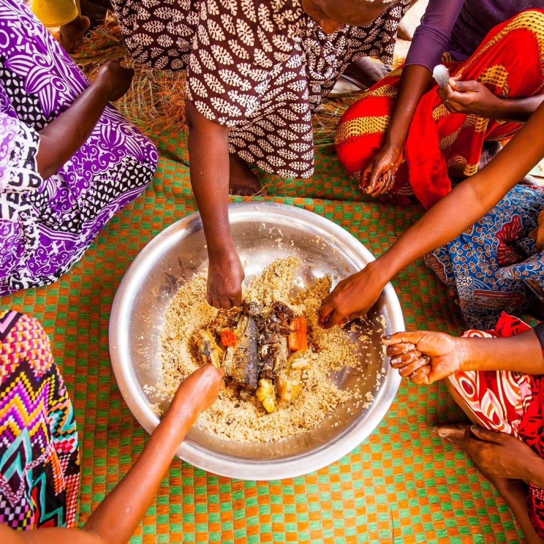 Tanzanian women eat out of a communal bowl of food during lunch time.